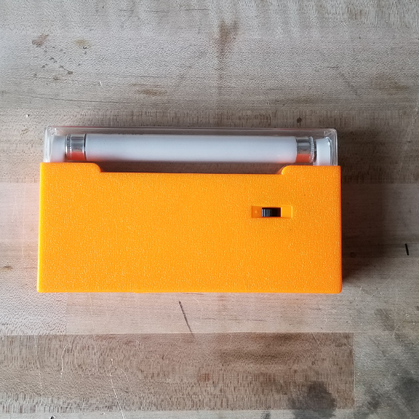 "photo of a small inspection lamp with an orange plastic body and a prominent black slide switch. It holds a 4W 6"" tube lamp and has a clear plastic protector over the tube."