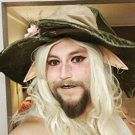 Selfie in full Taako makeup. I'm wearing a very light foundation with pink blush across the bridge of my nose and fake freckles. Black winged eyeliner and electric pink underliner. My cheeks are lightly contoured to my beard. I'm wearing downward elf ears with earrings in them and a floppy, moss-colored wizard hat.