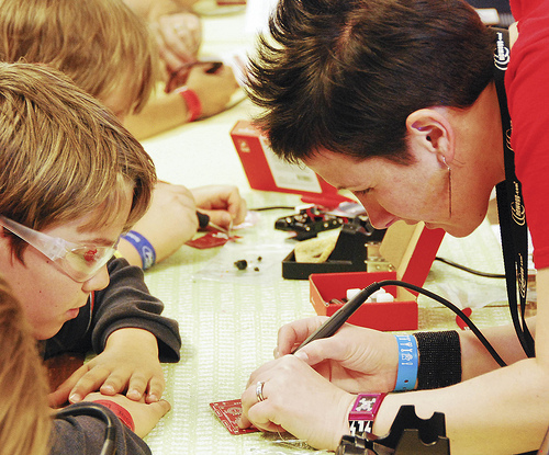 Lindsay helps a child solder in 2010