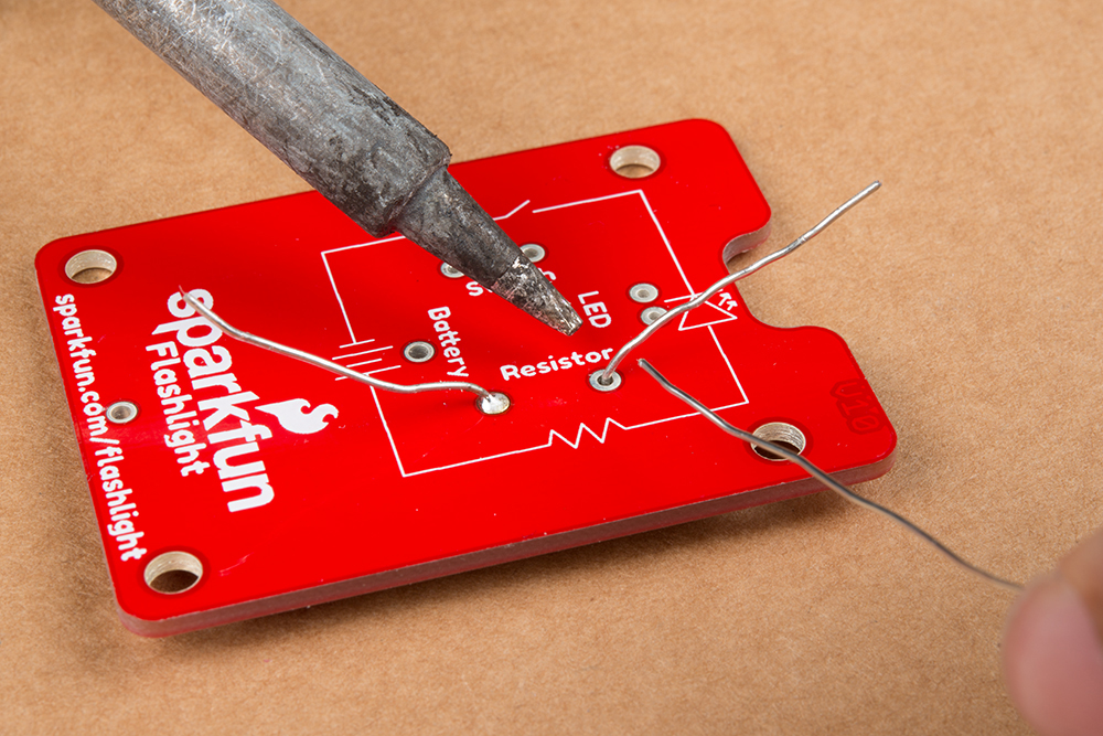 Photo of resistor being soldered to the board