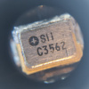 Microscope detail of a 4 pin SMD part that looks like a crystal resonator labeled SII C3562 with a cross in a circle