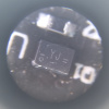 Microscope detail of an SMD part labeled YJ with various circles and dashes