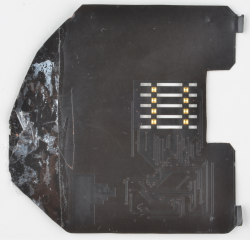 "detail photo of the backside of a deep insert credit card skimmer, also known as a shimmer. The board is black with gold contact finish, vaguely ""c"" shaped and shows signs of wear with remains of double-stick tape."