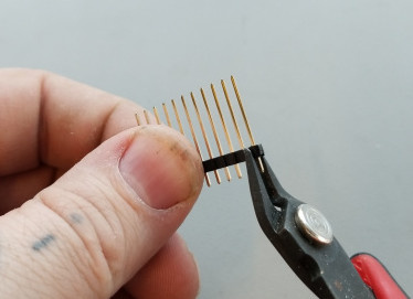 A hand holds a strip of pin headers while snipping one away using wire snips
