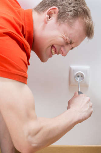 man sticking a screwdriver into a wall socket