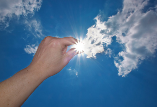 hand placing tiny sun in the sky