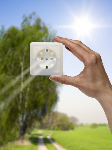 hand holding power outlet in front of the sun