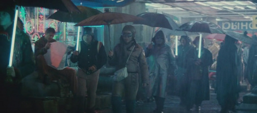 A screenshot from the movie Blade Runner showing people walking in the rain with neon glowing umbrellas
