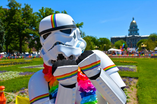 A stormtrooper poses for a photo with rainbow accents covering their armor.
