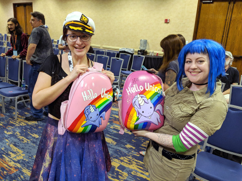 An event attendee and Angela show off their handmade Hello Unicorn backpacks