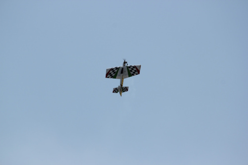 Balsa lightwweight powered aerobatic show plane in straight vertical climb above perfectly blue sky