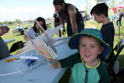 a child holding up his complete glider with a big smile on his face