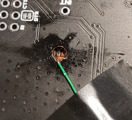 Wire soldered through hole onto pad