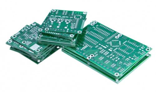 Three stacks of green PCBs