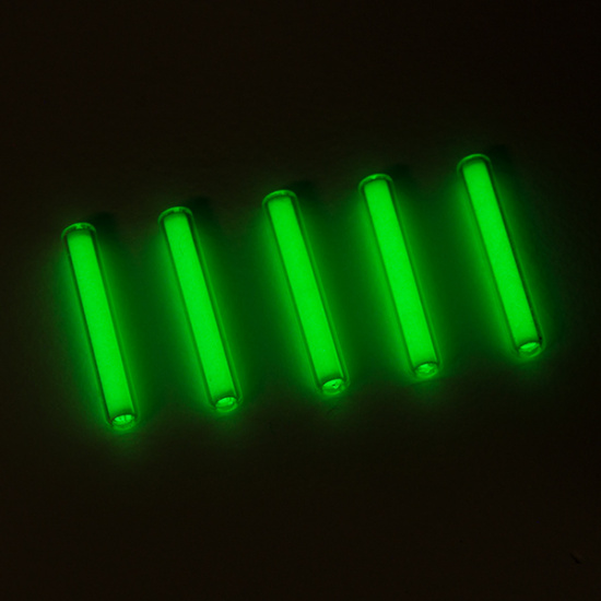 Several glowing green tritium tubes on a black background