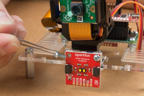 Time of flight sensor mounted to metal mounting brackets on mounting plate