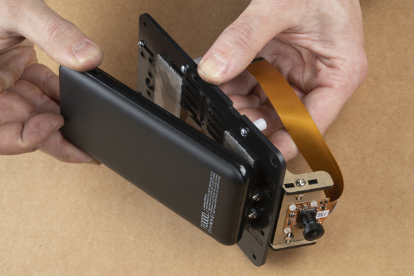 Demonstrating how to place the battery pack without touching the camera mount
