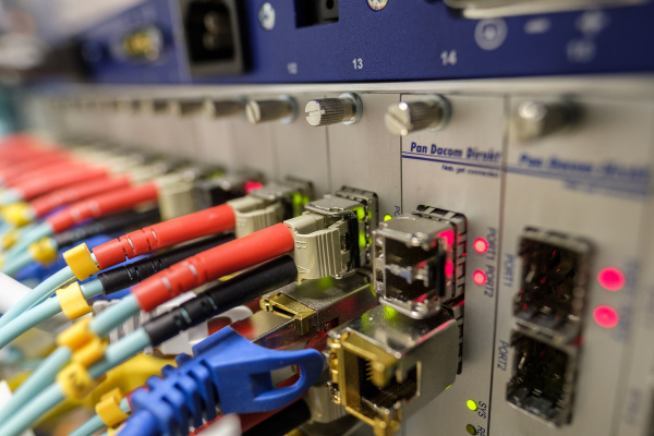 Stock image of fiber optic cables plugged into a piece of network equipment