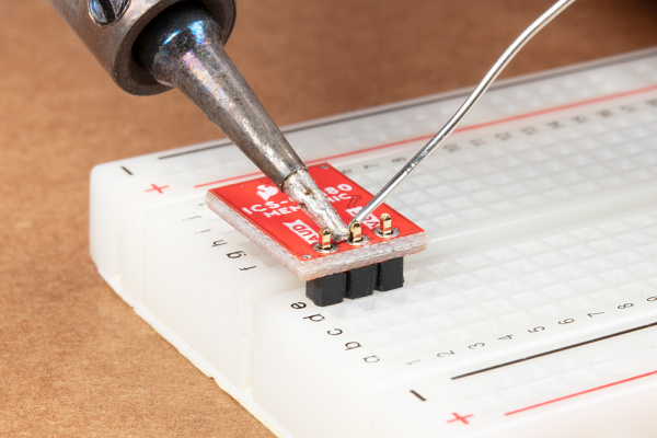 Straight header pins being soldered to MEMS microphone.