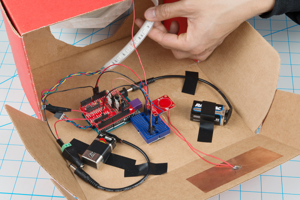 Circuit secured to bottom of cardboard box with electrical tape